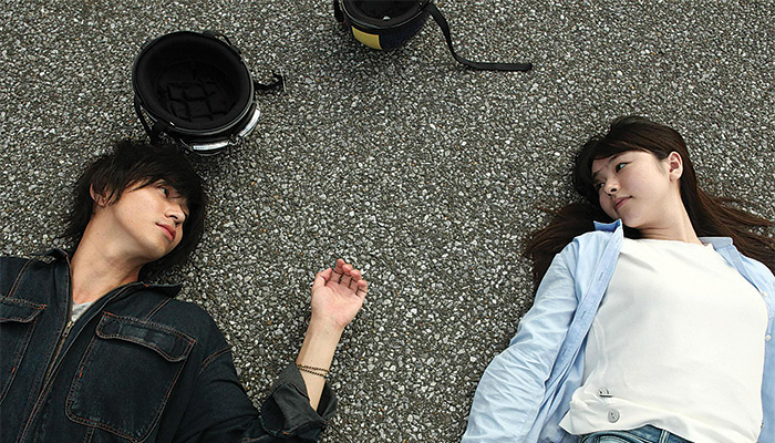 A boy and a girl lay on the asphalt staring at one another
