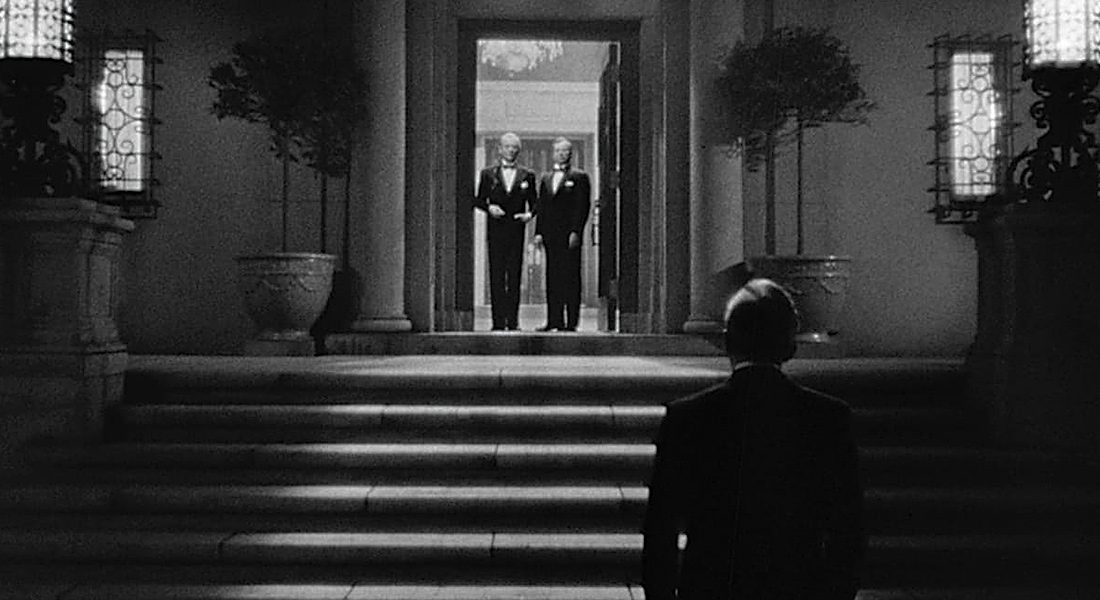 Two men in tuxedos stand in the doorway of a mansion