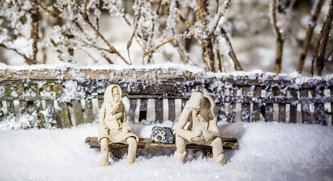 Two figures sit in a snow-covered scene