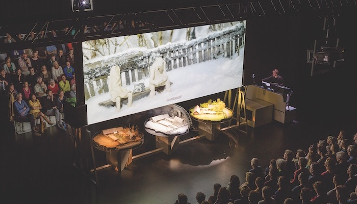 An audience is split into two groups, a large movie screen between them holds an image from a documentary film, and tables beneath the screen hold dioramas in a production still from Zvizdal [Chernobyl - so far so close] by Belgian performance group Berlin